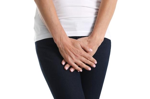 Jovem doente mantém as mãos pressionando o períneo para abaixar o abdômen. conceito de problemas de saúde médicos ou ginecológicos