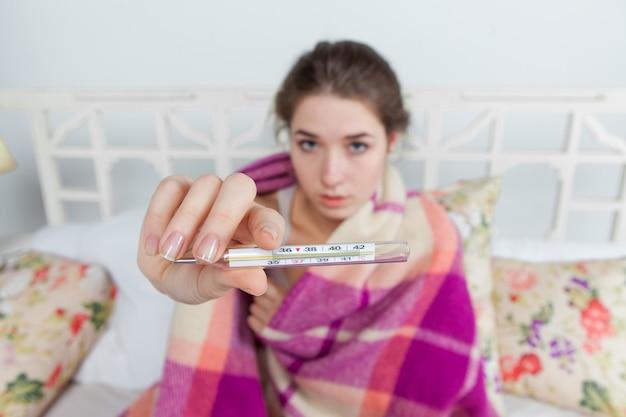 Jovem doente no cobertor com termômetro