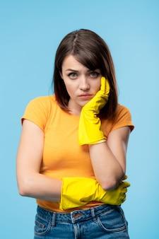 Jovem doente ou chateada com luvas de borracha amarelas e camiseta olhando para você com o rosto inexpressivo e isolado