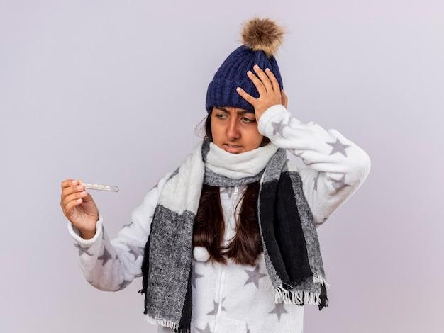 Jovem doente preocupada com chapéu de inverno com lenço segurando e olhando para o termômetro e colocando a mão na cabeça isolada no fundo branco