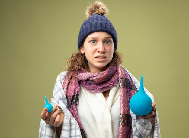 Jovem doente preocupada com túnica branca e chapéu de inverno com lenço embrulhado em xadrez segurando enemas isolados em verde oliva