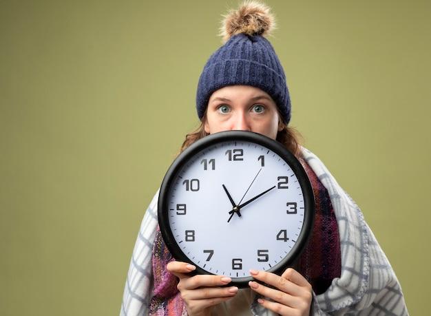 Jovem doente preocupada vestindo túnica branca e chapéu de inverno com lenço coberto no rosto com relógio de parede envolto em xadrez isolado em verde oliva