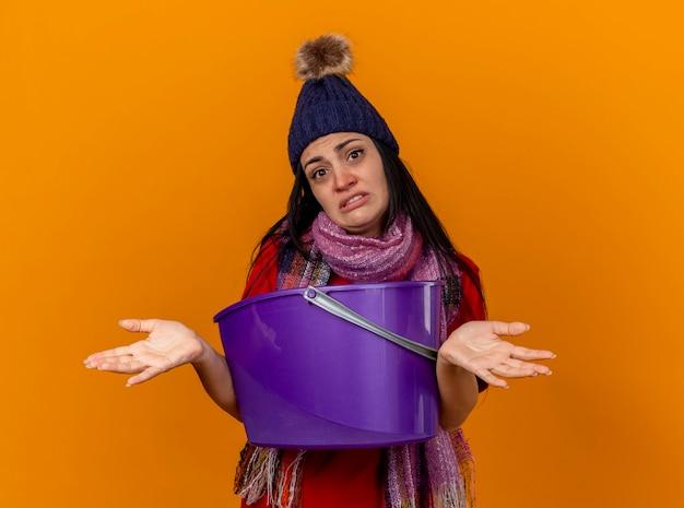 Jovem doente sem noção usando chapéu de inverno e lenço segurando um balde de plástico, tendo náuseas, olhando para a frente, mostrando as mãos vazias isoladas na parede laranja