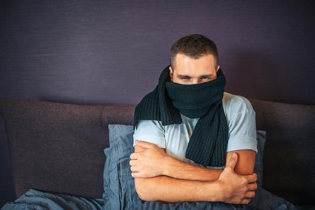 Jovem doente senta-se na cama e cobre a boca com cachecol. está frio no quarto. cara mantém as mãos cruzadas. ele ficou com frio. jovem sofre.
