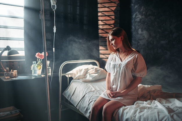 Jovem doente sentada na cama do hospital, pingando