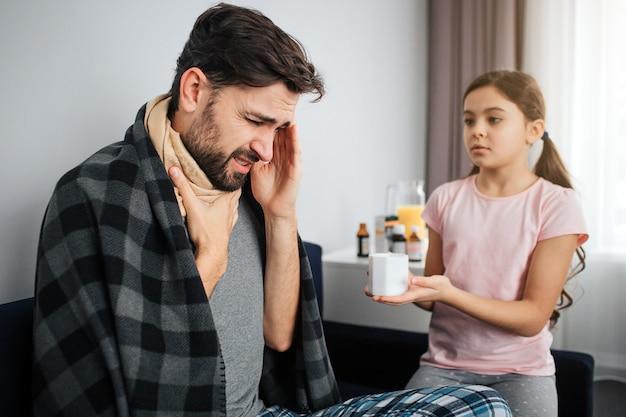 Jovem doente sentar no sofá com sua filha. cara de mãos dadas na garganta e cabeça. menina pequena séria olha para ele. ela dá copo branco com tratamento.