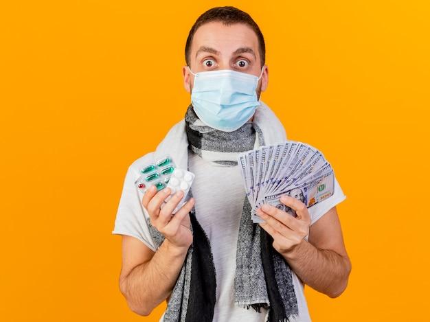 Jovem doente surpreso com chapéu de inverno e máscara médica segurando dinheiro com comprimidos isolados em fundo amarelo