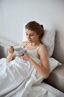 Jovem doente tomando café da manhã na cama, apoiada em um travesseiro macio