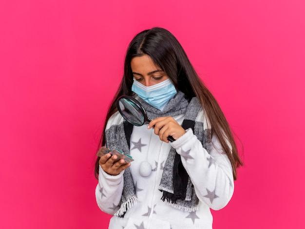 Jovem doente usando máscara médica com lenço segurando e olhando comprimidos com lupa isolada em rosa