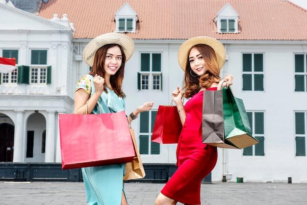 Jovem, dois, mulher asian, com, chapéu, segurando, muitos, bolsas para compras