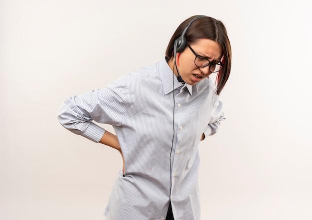 Jovem dolorida no call center usando óculos e fone de ouvido, olhando para baixo, colocando as mãos na cintura, sofrendo de dor isolada no branco