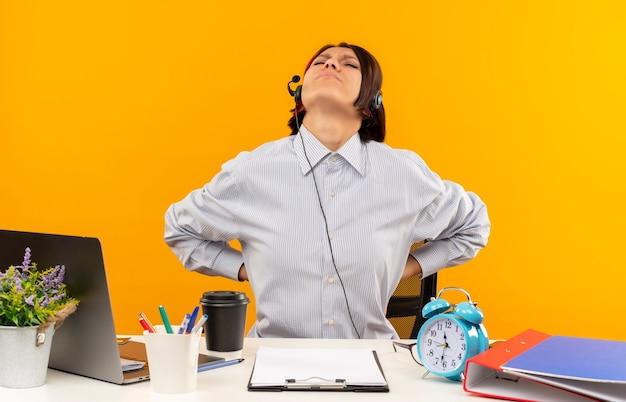 Jovem dolorida no call center usando um fone de ouvido, sentada na mesa, colocando as mãos nas costas com os olhos fechados, isolados em laranja