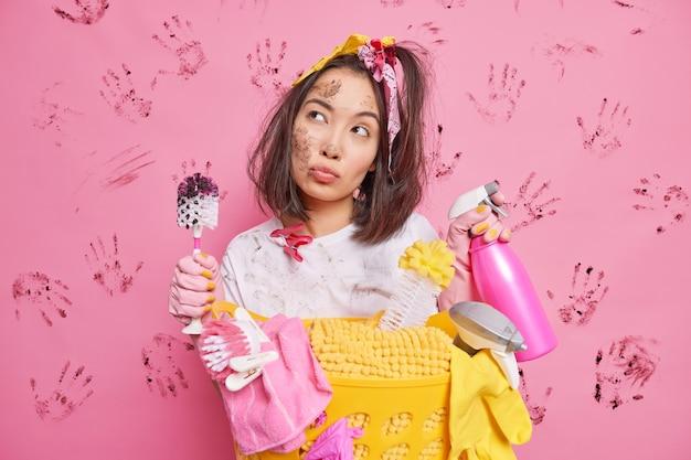 Jovem dona de casa asiática séria e pensativa segurando detergente e a escova parece pensativa e faz poses de rosto sujo perto do cesto de roupa suja isolado sobre a parede rosa