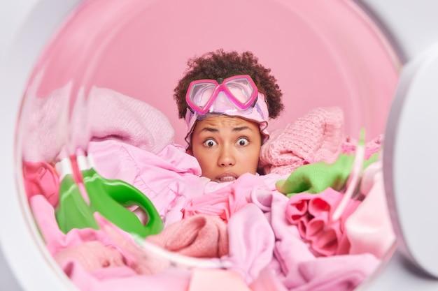 Jovem dona de casa atordoada e preocupada com uma expressão de medo se escondendo em uma pilha de poses de roupa suja de dentro da máquina de lavar usa óculos de mergulho na testa ocupada com o trabalho doméstico diário