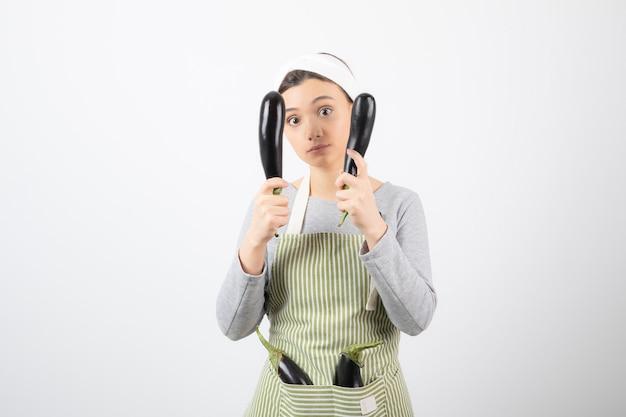 Jovem dona de casa brincando com berinjelas frescas no branco