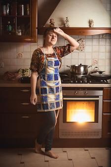 Jovem dona de casa cansada em pé perto de um forno de trabalho