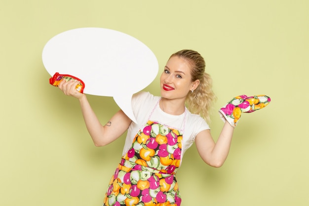 Jovem dona de casa com camisa e capa colorida segurando uma enorme placa branca com um sorriso no verde