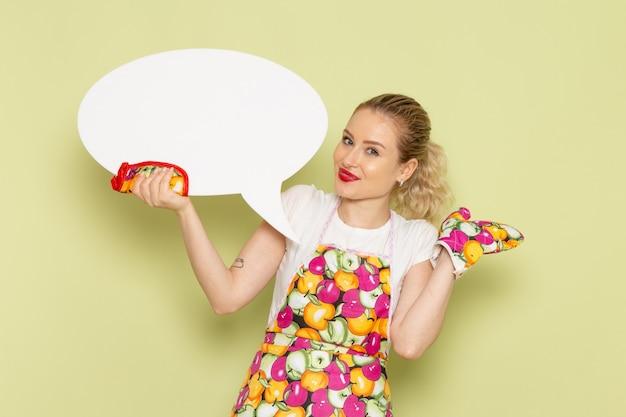 Jovem dona de casa com camisa e capa colorida segurando uma placa branca no verde