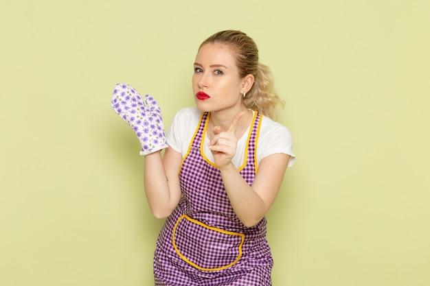 Jovem dona de casa com camisa e capa colorida usando luvas de cozinheiro com aviso em verde