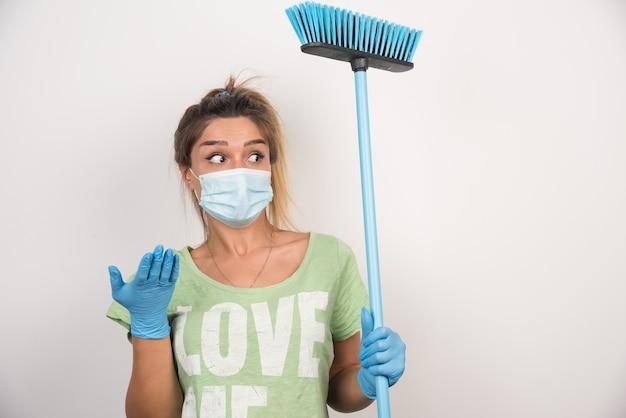 Jovem dona de casa com máscara e vassoura apontando para o lado com a mão na parede branca.
