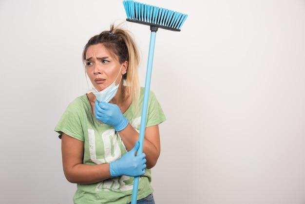 Jovem dona de casa com máscara e vassoura, olhando de lado com expressão confusa na parede branca.