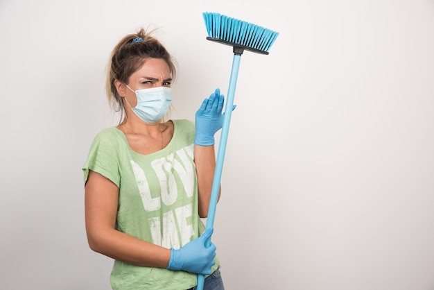 Jovem dona de casa com máscara e vassoura, olhando para frente com expressão confusa na parede branca.