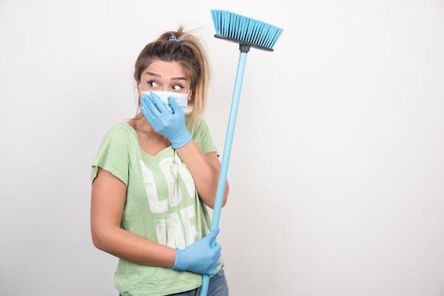 Jovem dona de casa com máscara e vassoura segurando o rosto dela.