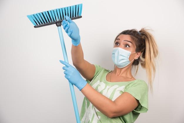 Jovem dona de casa com máscara, fazendo trabalhos domésticos com vassoura na parede branca.