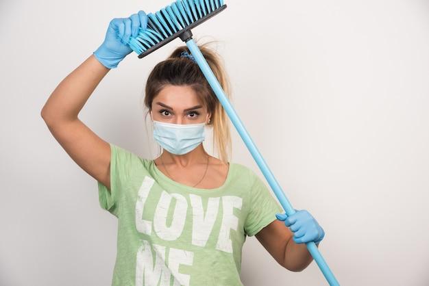 Jovem dona de casa com máscara segurando a ponta da vassoura na parede branca.