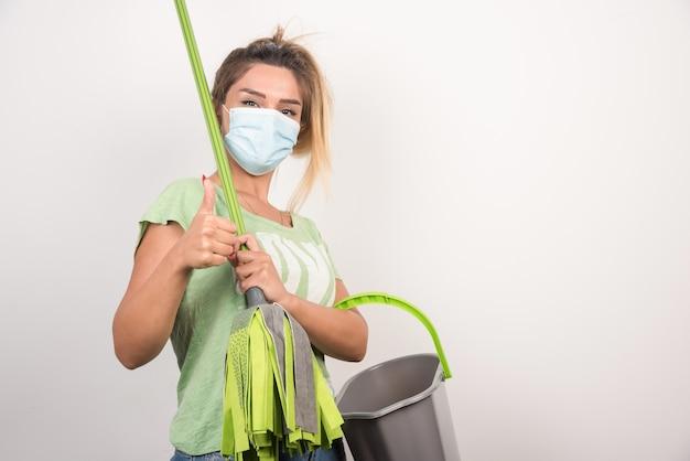 Jovem dona de casa com máscara segurando o esfregão e fazendo os polegares para cima.