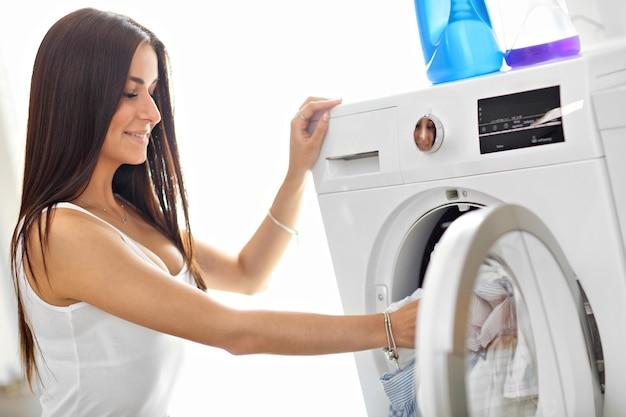 Jovem dona de casa com roupa suja ao lado da máquina de lavar