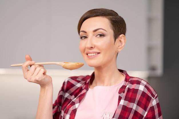 Jovem dona de casa com um penteado curto testando uma comida enquanto prepara o jantar para a família no
