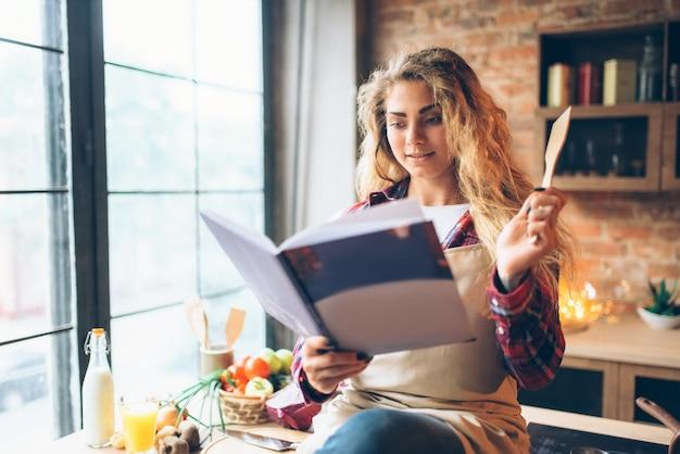 Jovem dona de casa de avental lendo livro de receitas
