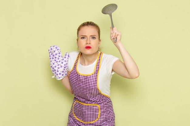 Jovem dona de casa em camisa e luvas de capa roxa ameaça com colher no verde