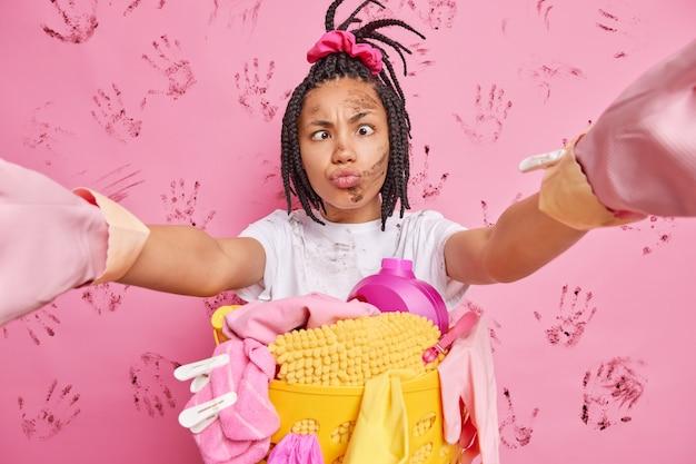 Jovem dona de casa engraçada faz careta para a câmera, estende os braços, selfie cruza os olhos e faz beicinho poses de lábios perto do cesto de roupa suja isolado sobre a parede rosa