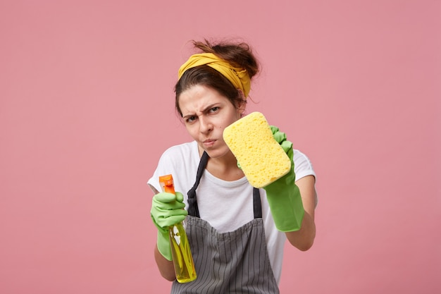 Jovem dona de casa engraçada usando roupas casuais, avental e luvas protetoras de borracha obcecada por limpeza, olhando com olhar meditativo enquanto arruma a casa até que esteja totalmente limpa