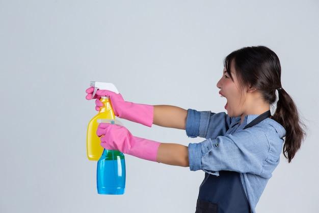 Jovem dona de casa está usando luvas amarelas durante a limpeza com o produto de limpeza na parede branca.