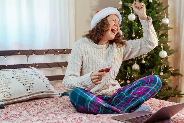 Jovem dona de casa feliz com cartão de crédito fazendo compras online de natal