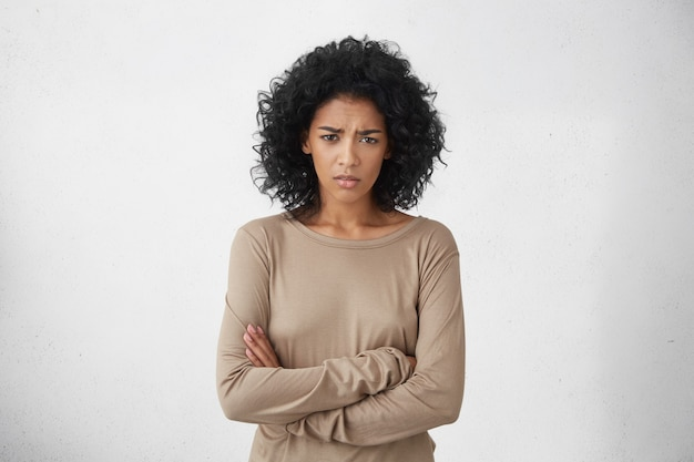 Jovem dona de casa irritada com raiva de braços cruzados