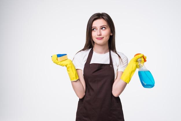 Jovem dona de casa limpando com tapete e detergente isolado