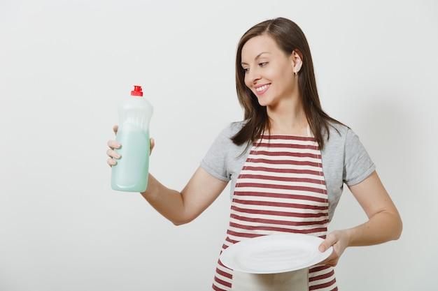 Jovem dona de casa no avental listrado isolado. mulher governanta segura garrafa com líquido de limpeza para lavar louça, prato redondo vazio branco