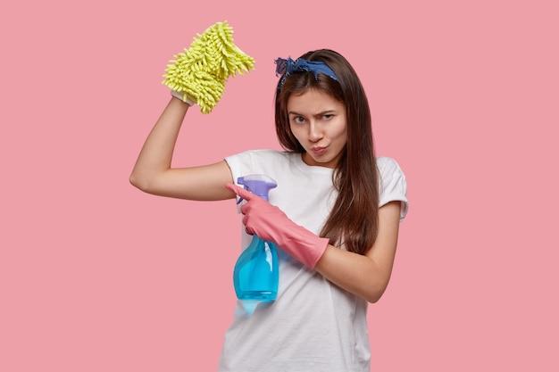 Jovem dona de casa sombria aponta para um músculo com expressão séria e ofensiva, zangada com o marido que não a ajuda na limpeza da casa, segura detergente