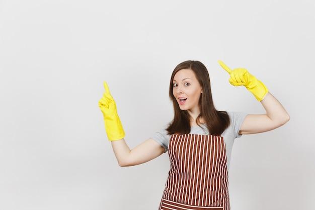 Jovem dona de casa sorridente atraente no avental listrado, luvas amarelas isoladas. bela governanta apontando o dedo indicador para o lado
