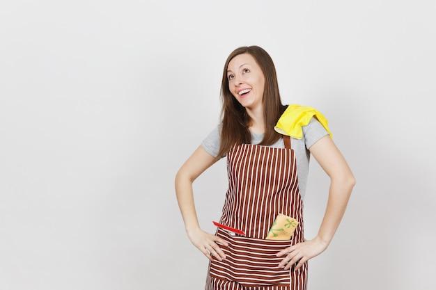 Jovem dona de casa sorridente com avental listrado com pano de limpeza, rodo e luvas amarelas no bolso isolado