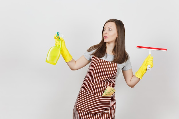 Jovem dona de casa sorridente com luvas amarelas, avental listrado, pano de limpeza no bolso isolado