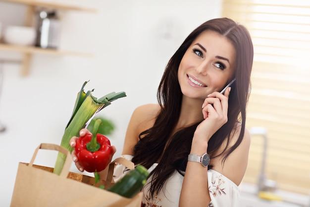 Jovem dona de casa sorridente em cozinha moderna
