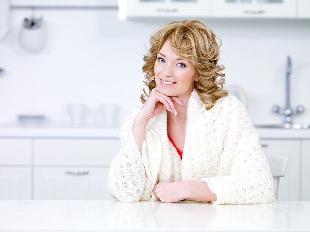 Jovem dona de casa sorridente em vestido doméstico branco sentada na cozinha