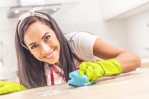 Jovem dona de casa sorridente, inclinada sobre a mesa sendo limpa com detergente e esponja, com luvas de borracha, olhando para a câmera.