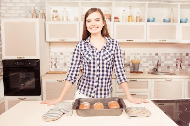 Jovem dona de casa sorridente na cozinha com pão assado