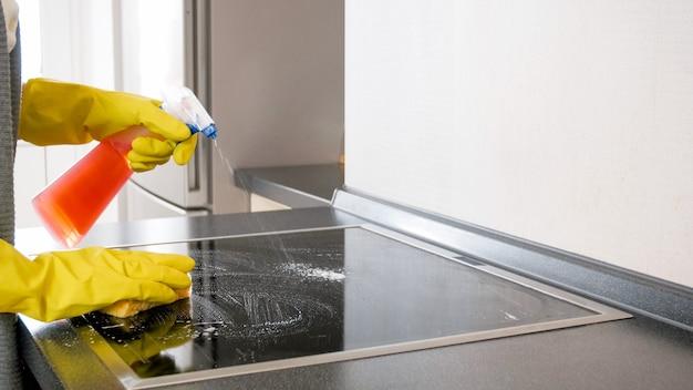 Jovem dona de casa usando spray químico durante a limpeza do fogão elétrico na cozinha.